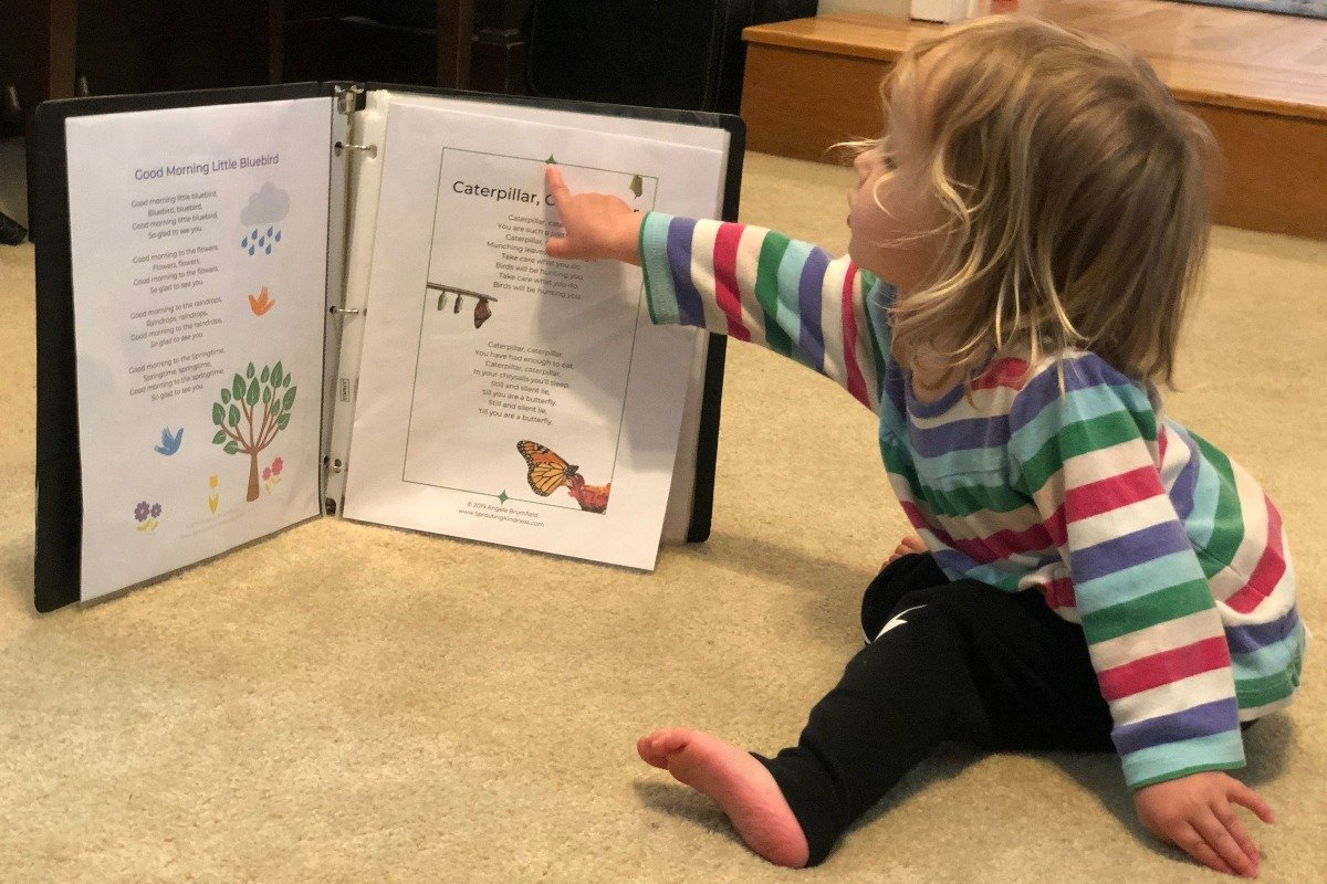 a girl points to a preschool spring songs and fingerplays binder of printables
