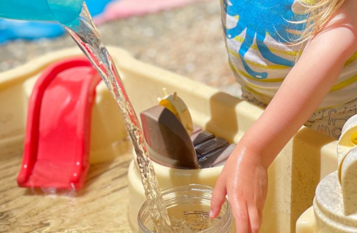 a preschooler pours water into a cup